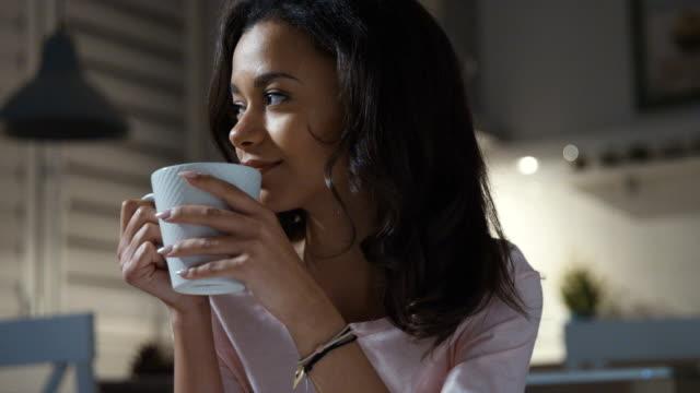 Happy young woman wearing pajamas sitting with tea/chocolate/coffee mug, smiling. video