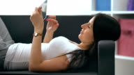 Happy young woman with tablet pc laying on sofa video