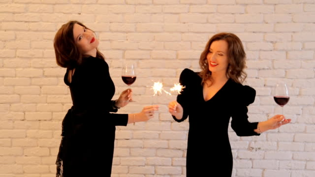 Happy young women with sparklers and wine glasses on party. video