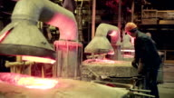 Hard work in the foundry. Worker operates in blast furnace workshop of metallurgical plant, foundry video