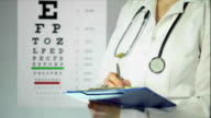 Hard-working optician prescribing medication to patient at clinic, healthcare video