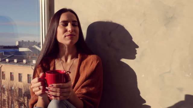 Harmonious woman enjoying a good cup of coffee in the morning while sitting on the windowsill video