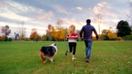 Have fun with your beloved dog. Young multi-ethnic couple running in the park. Steadicam slow motion shot. Back view video