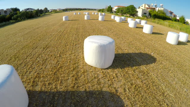 Haystack carefully packed after harvesting campaign on farm field, aerial view video