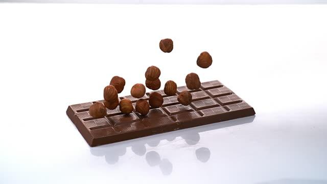 Hazelnuts falling on Milk Chocolate tablet, Slow motion 4K video