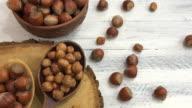 Hazelnuts in a bowl near a spoon peeled walnut on a wooden surface video