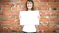 hd girl in front of bricks wall with copyspace sheet video