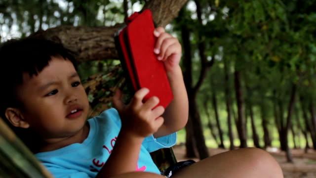 HD:Asian cute girl play tablet on the beach video