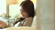HD:Asian cute women play tablet on the bed. video