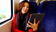 HD:Asian cute women play tablet on the train. video