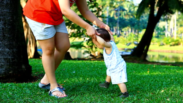 HD:Asian mother helping baby walk in the park.. video