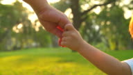 HD:Baby boy holding mother hand and running in the park. video