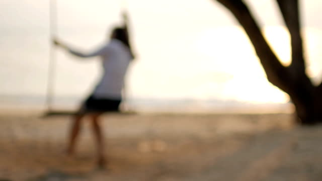 HD:Blurred Woman on swing on the beach with sea at sunset time , slow motion , relaxation concept video