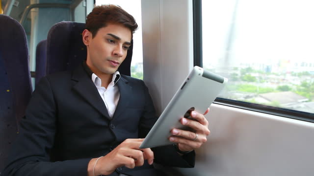 HD:Businessman play tablet on the train. video
