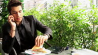 HD:Businessman talking on mobile phone during meal outdoors video