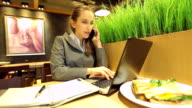 HD:Businesswoman multitasking with laptop cellphone and taking note. video