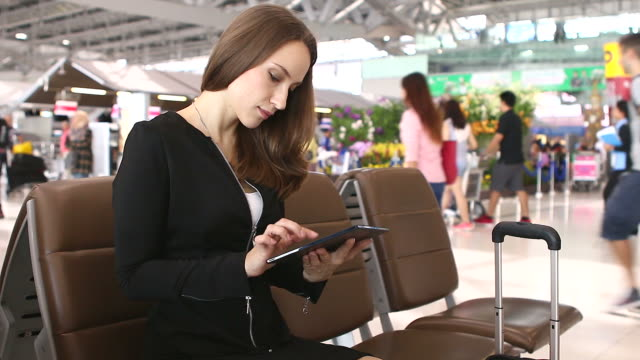 HD:Businesswoman playing with tablet while waiting for her flight. video