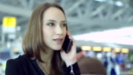 HD:Businesswoman talking by using mobile phone at airport. video