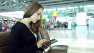 HD:Businesswoman working by using mobile phone at airport.. video