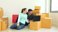 HD:Couple checking data in notebook decorate new house. video