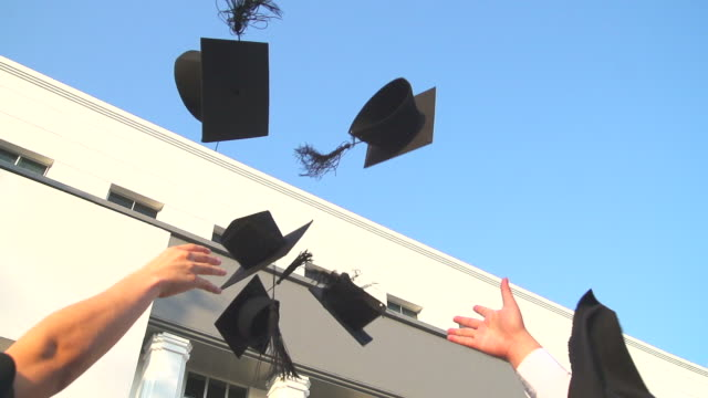 HD:Graduates throwing graduation hats in the air. video