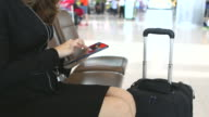 HD:Hand of businesswoman playing with tablet while waiting for her flight. video