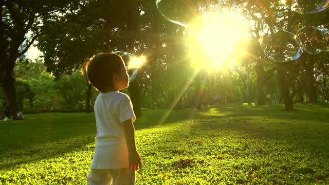 HD:Little boy in the sunset catches soap bubbles. video
