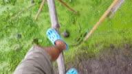 HD:Man walking cross river on bamboo bridge. video