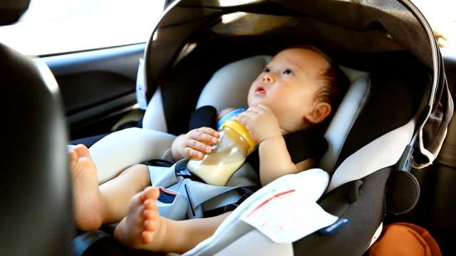 HD:Portrait of a little boy drinking milk in the car. video