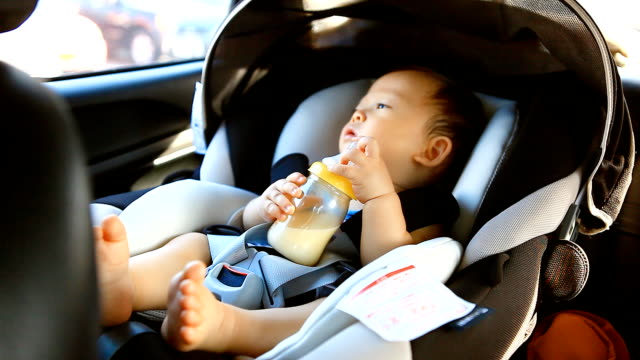 HD:Portrait of a little boy drinking milk in the car. video
