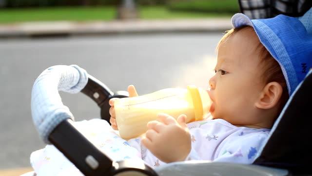HD:Portrait of a little boy drinking milk in the park. video