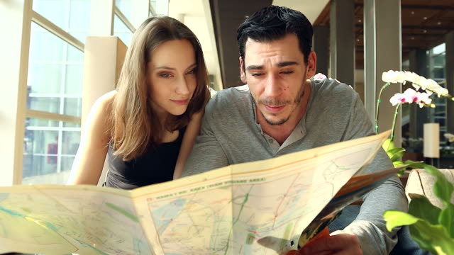 HD:Portrait of tourist couple checking city map at lobby hotel. video