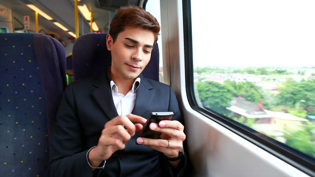 HD:Young businessman playing mobile phone on the train. video