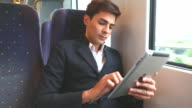 HD:Young businessman using tablet on the train. video