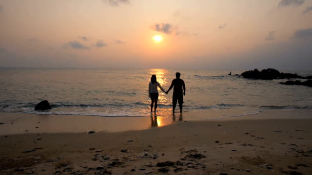 HD:Young Couple Walking on Beach to the sea holding hands at sunset time ,slow motion ,relaxation concept video