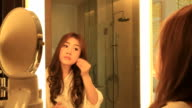 HD:Young woman applying makeup with brush in bathroom. video