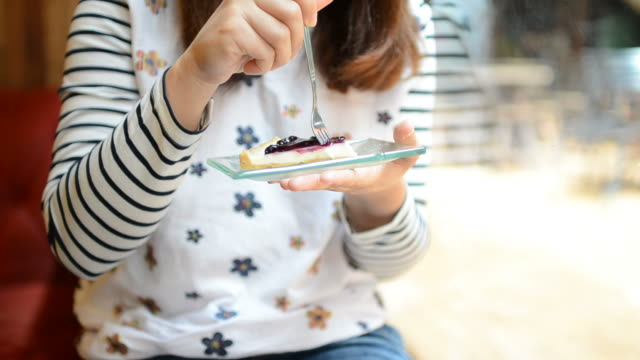 HD:Young woman eating blueberry cheese pie cake video