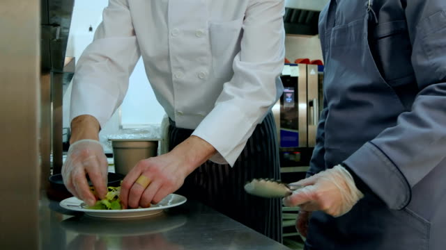 Head chef showing his assistant how to serve the salad video