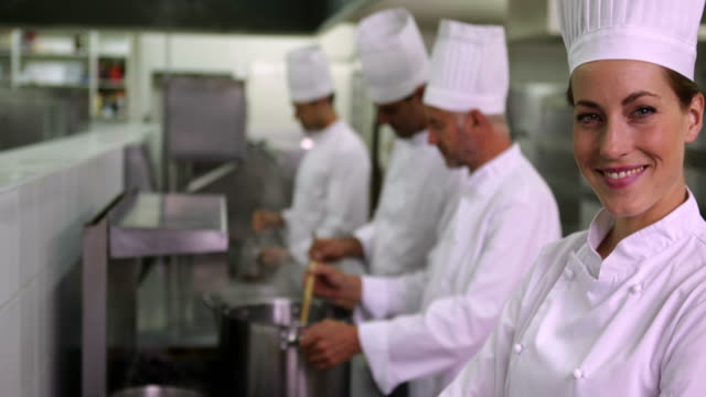 Head chef smiling at camera with team behind her video