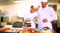 Head chef watching his student pour cream into pastry case video