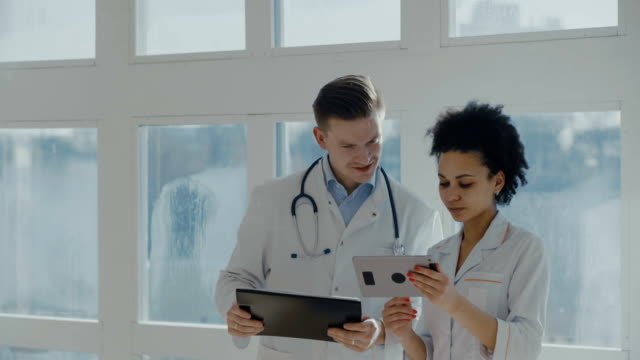 Healthcare, medical: Doctors met in a clinic or hospital, discussing and looking tablet pc. video