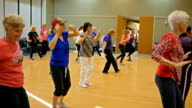 Healthy active seniors dance in exercise class video