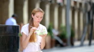 Healthy lunch slender woman. A young woman eating a salad on a city center. video