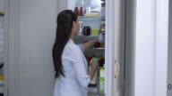 Healthy woman at home taking groceries from the fridge video