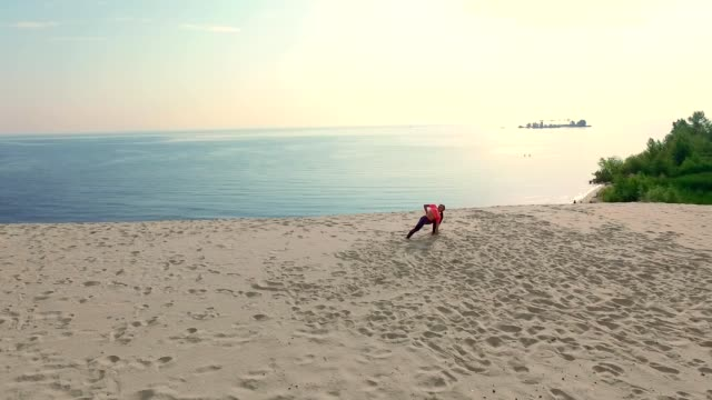 Healthy, young beautiful woman in sunglasses meditating, stretching, practicing yoga on the sea beach, at sunrise, Makes exercises for balance, coordination, deep muscle tone video