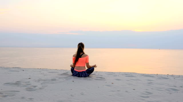 Healthy, young beautiful woman meditating, practicing yoga on the beach, by the sea, at sunrise, Relaxes muscles, mind, acquires the harmony of soul and body video