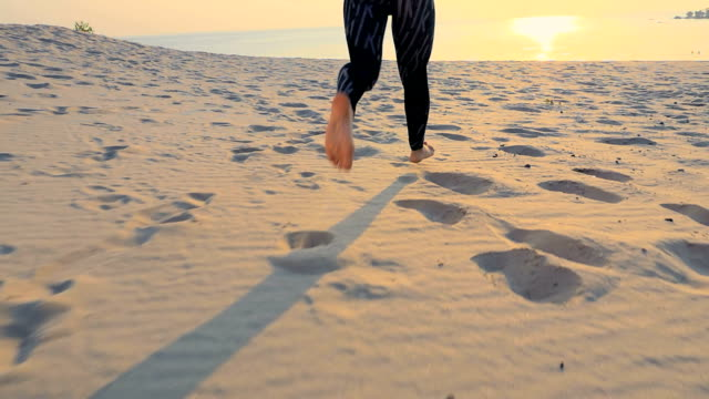 Healthy, young sports beautiful woman runs along the sand, on the beach, in summer, towards the sun, at the sunrise. Close-up of foot video