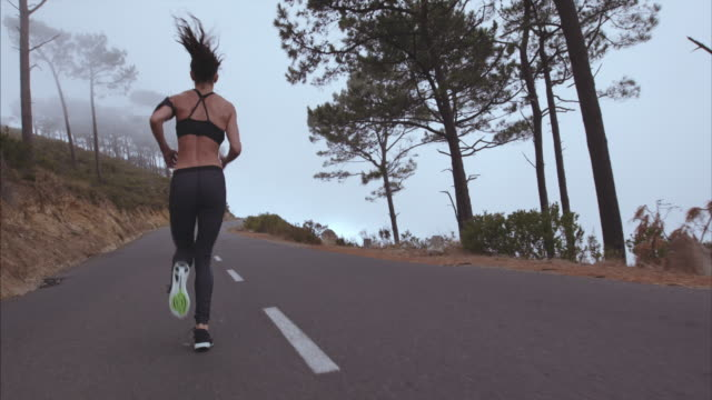 Healthy young woman running on country road video