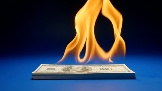 SLOW MOTION: Heap of paper money (US dollar) flaming on a table video