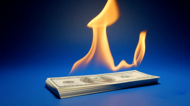 SLOW MOTION: Heap of paper money (US dollar) flaming video